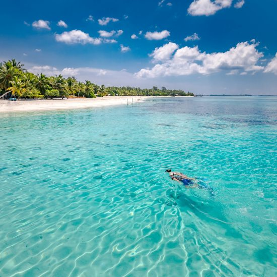 Caucasian couple of tourists snorkel in crystal turquoise water near Maldives Island